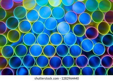 Drinking straw bundle from behind with colored illuminated, blue
