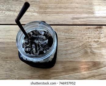 Drinking straw with coffee bottle on table