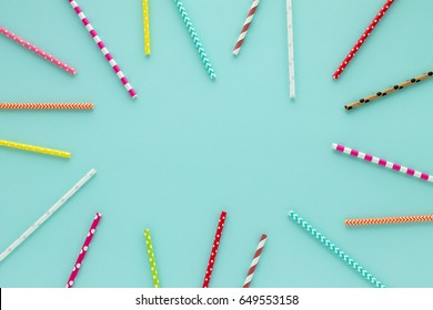 Drinking straws for party on blue pastel background with copy space. Top view of colorful paper disposable eco-friendly straws for summer cocktails.