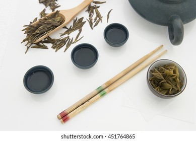 Drinking tea displays. Tea set of stoneware pot and cups. Remove brewed tea leaves in small bowl and roasted tea in bamboo spoon. Chinese green tea name Longjing or Dragon Well tea. White background.