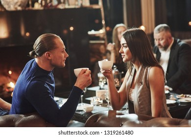 Drinking tea and looking at each other. Beautiful couple. Family friends having nice time in beautiful luxury modern restaurant.