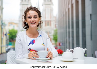 Drinking tea. Young beautiful brunette woman holding cup of beverage while sitting at cafe.