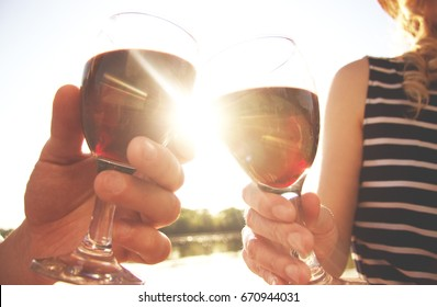 Drinking together. Low angle view of beautiful young couple clinking glasses with wine while sitting on the beach with sunlight on background.