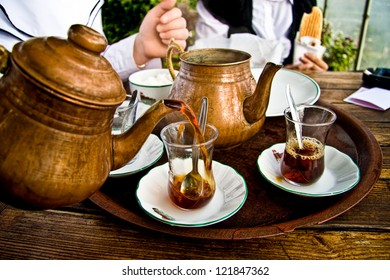 Drinking traditional Turkish Tea with Turkish tea cup and copper tea pot, and eating toast with friends.