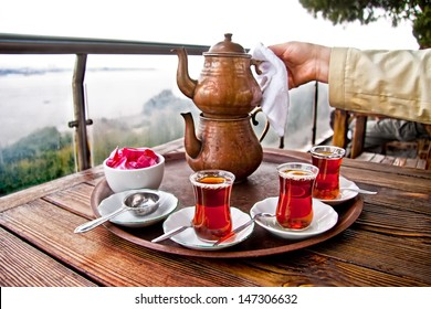 Drinking Traditional Turkish Tea with Turkish tea cup and copper tea pot