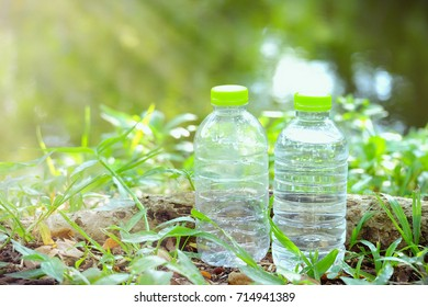 Drinking water bottle in the green garden with soft light with water view and nature background