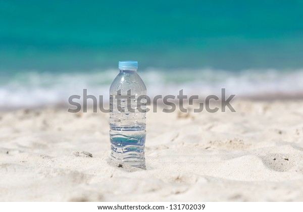 Drinking water in bottle on sand on beach