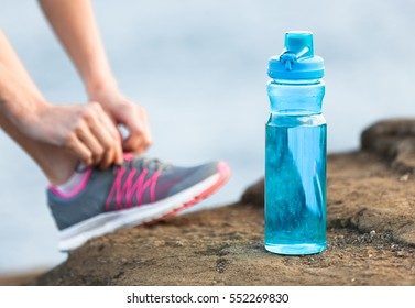 Drinking water concept. Bottle of water with runner tying shoe in the background. Focus on water.