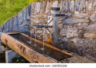 Drinking water fountain in vintage town Murren in highland Switzerland