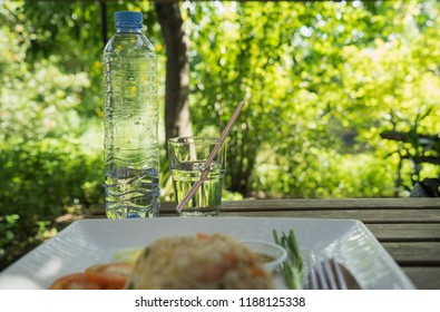 Drinking water glass with plastic straw and pet plastic bottle, blur fried rice plate menu on table in outdoor garden restaurant. Disposable single use plastic straws, health and environmental concept