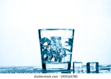 drinking water into a clear glass with ice on the table on a white background with copy space.