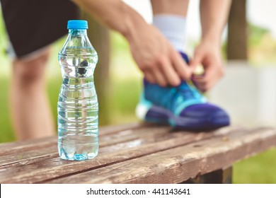 Drinking water from the plastic bottle in the park and running footwear close up. City outdoor workout and fitness healthy nutrition concept. Female athlete tying sport shoes laces before training.