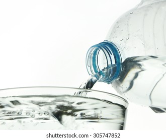 Drinking water is poured from a bottle into a glass on white background
