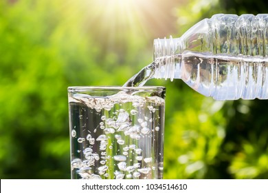 Drinking water pouring from bottle into glass on blurred fresh green nature background, healthy drink concept