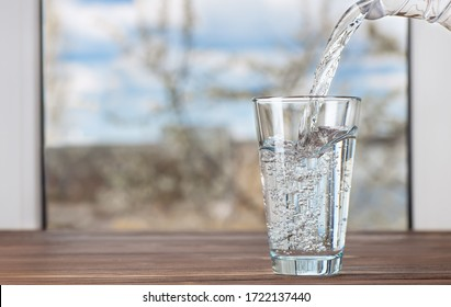drinking water pouring from jug into glass on table against the window indoors