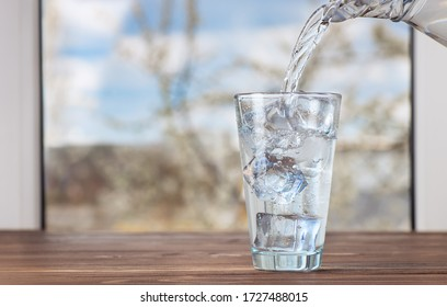 drinking water pouring from jug into glass with ice on the table against the window indoors