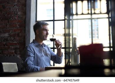 Drinking wine in a restaurant. Man drinking wine