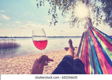 drinking wine, woman with red wine in hammock at the beach