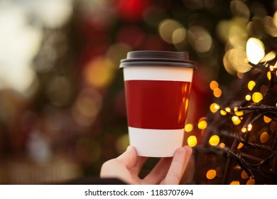 drinks, beverages, woman hand holding take away coffee cup outdoors Christmas bokeh and lights in backg