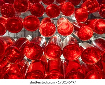 Drinks bottled and stored together. Bottles of red beverage stored on special shelf. Alchohol, non-alchohol drinks in bar, restaurant. View from below. Bottles of wine in winery. Beverage industry