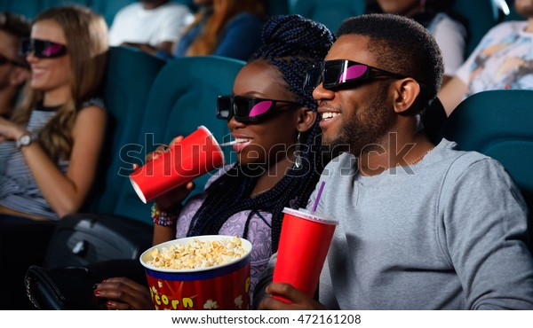 Drinks and corn! Portrait of a cheerful African couple watching a 3D movie enjoying their drinks and popcorn