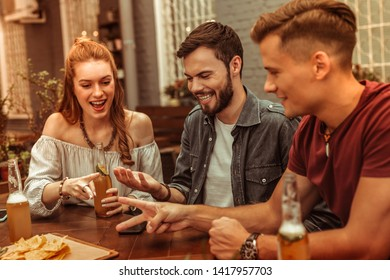 Drinks with friends. Charming red-haired appealing young lady and two happy beaming attractive guys sitting at the bar with drinks and having fun