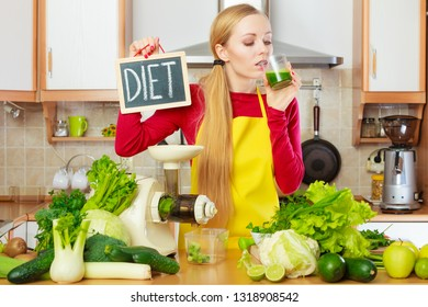 Drinks good for health, diet breakfast concept. Young woman in kitchen holding green healthy vegetable smoothie juice glass next to diet sign.