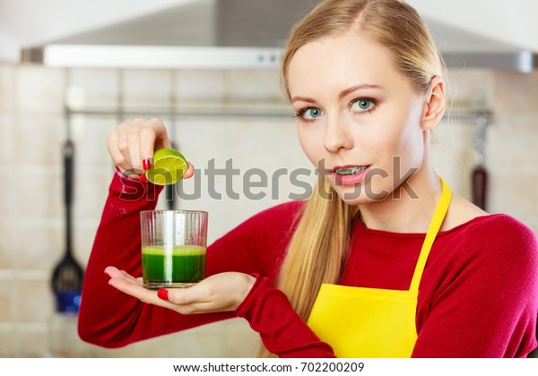 Drinks good for help, diet breakfast concept. Young woman in kitchen holding green healthy vegetable smoothie juice in glass