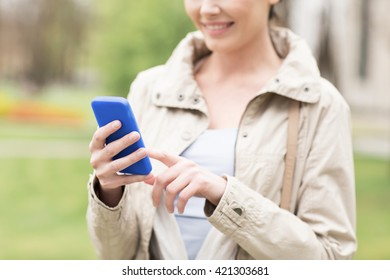 drinks, leisure, technology and people concept - smiling woman calling or texting message on smartphone in park