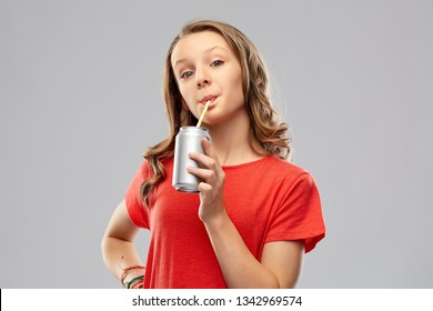 drinks and people concept - teenage girl in red t-shirt drinking soda from can through paper straw over grey background