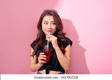 drinks, people and lifestyle concept - close up of happy woman drinking cola with straw at home