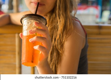 drinks, people and lifestyle concept - close up of woman drinking ice tea from plastic cup with straw at cafe. Selective focus.