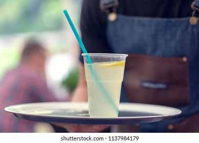 Drinks in plastics on a tray. Waiter serves drinks in a cafe.