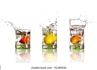Drinks with splashing citrus fruits over white