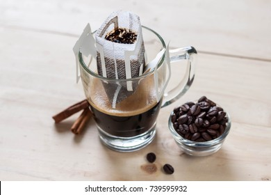 Drip or brewed coffee on wooden texture, paper dripping bag on a cup