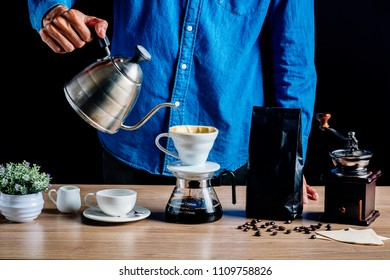 Drip brewing coffee concept.Barista pouring hot water on roasted coffee ground with filter on black background.