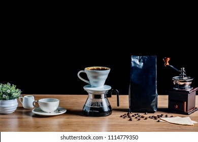 Drip brewing coffee concept.Wooden desk with old vintage coffee grinder,coffee beans,paper and cup of coffee on black background.