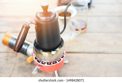 drip coffee barista pouring water on filtered brewing / make cup hand drip coffee in glass jar on weighing scale and  wooden table