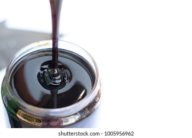 Dripping black treacle or molasses in glass.  Molasses is the final product from the sugarcane extraction process of sugar factory industrial. Background with copy and text space. - Selective focus.