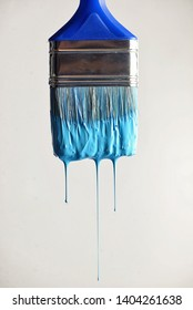 Dripping blue water paint from brush