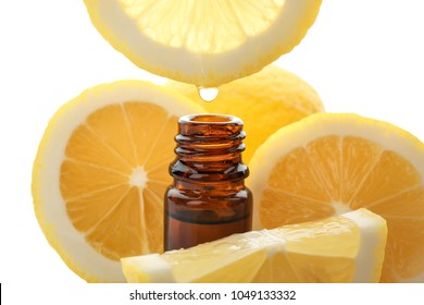 Dripping citrus essential oil into bottle on white background