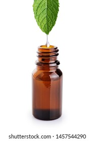 Dripping essential oil into bottle on white background. With clipping path.