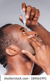 Dripping his eyes with eye drops. Side view of young African man applying eye drops while standing against grey background