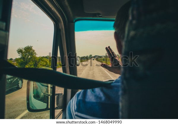 A drive of a bus from Chisinau to Tiraspol is waving with hand to other van or bus drivers to greet them or say hello. Sunny day on a road waving to others.