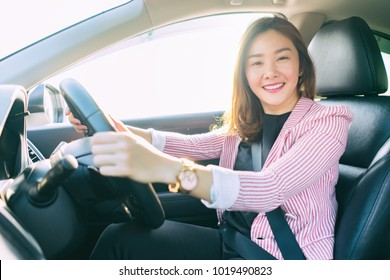 Drive a car with confident and beautiful Smiling Asian women. Rear view of attractive young girl in casual wear looking  at camera,Right hand wheel, driving a cars concept