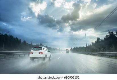 Drive car in rain on asphalt wet road. Clouds and sun.