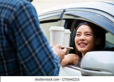 Drive car thru coffee service.Staff send coffee mugs to customer in vehicle.