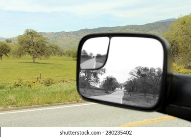 A drive in the country with a beautiful landscape of green grass and a rear view mirror showing a landscape in black and white.
