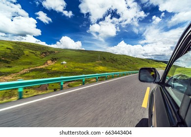 Drive on the road in the Tibetan plateau, the green grassland, the weather sunny blue sky white clouds, motion blur