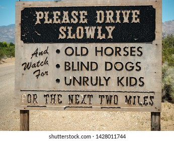 A drive slowly road sign cautioning about old horses, blind dogs, and unruly kids